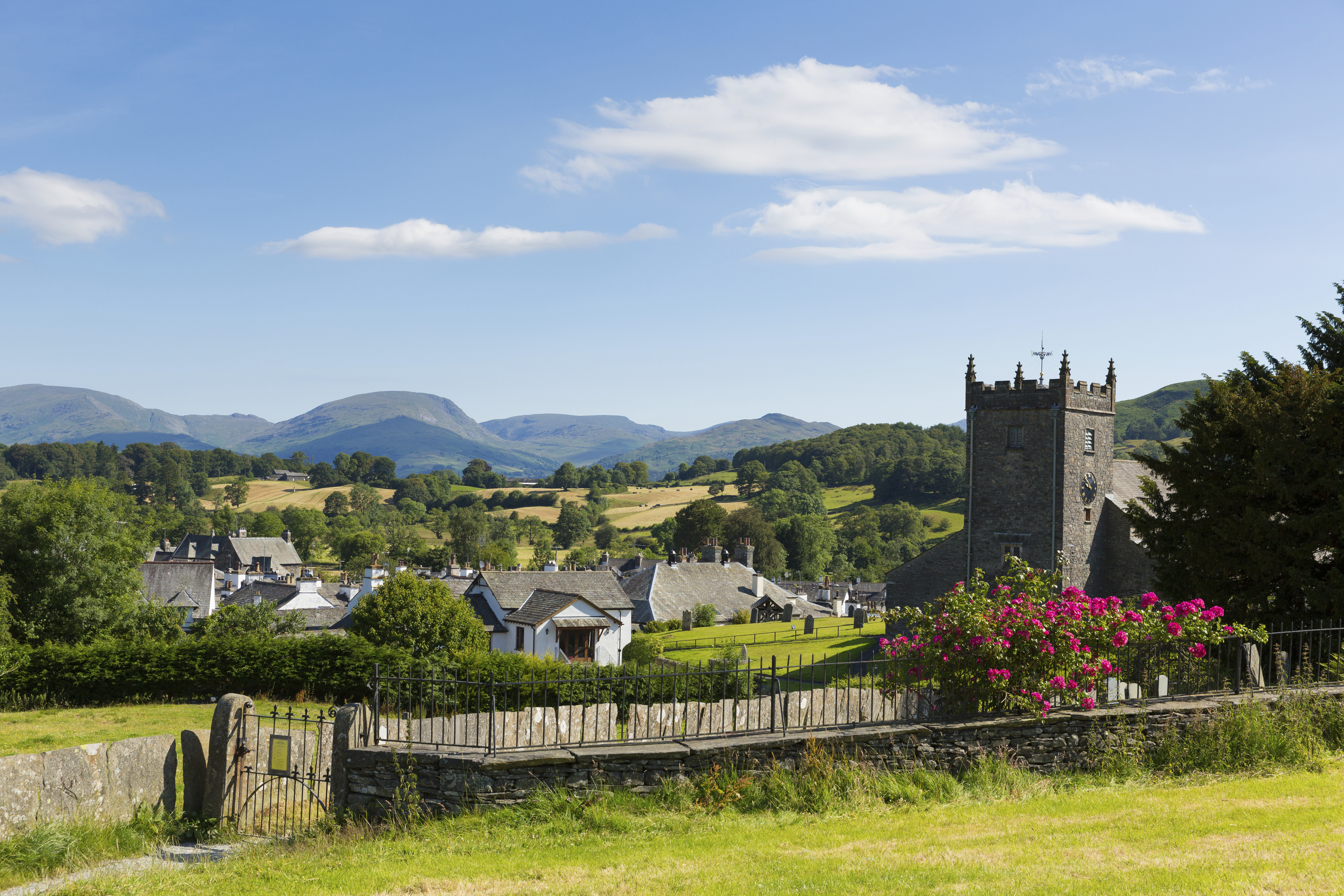 Traditional British village in English Lake District of Hawkshead Cumbria UK in summer with blue sky church and red roses