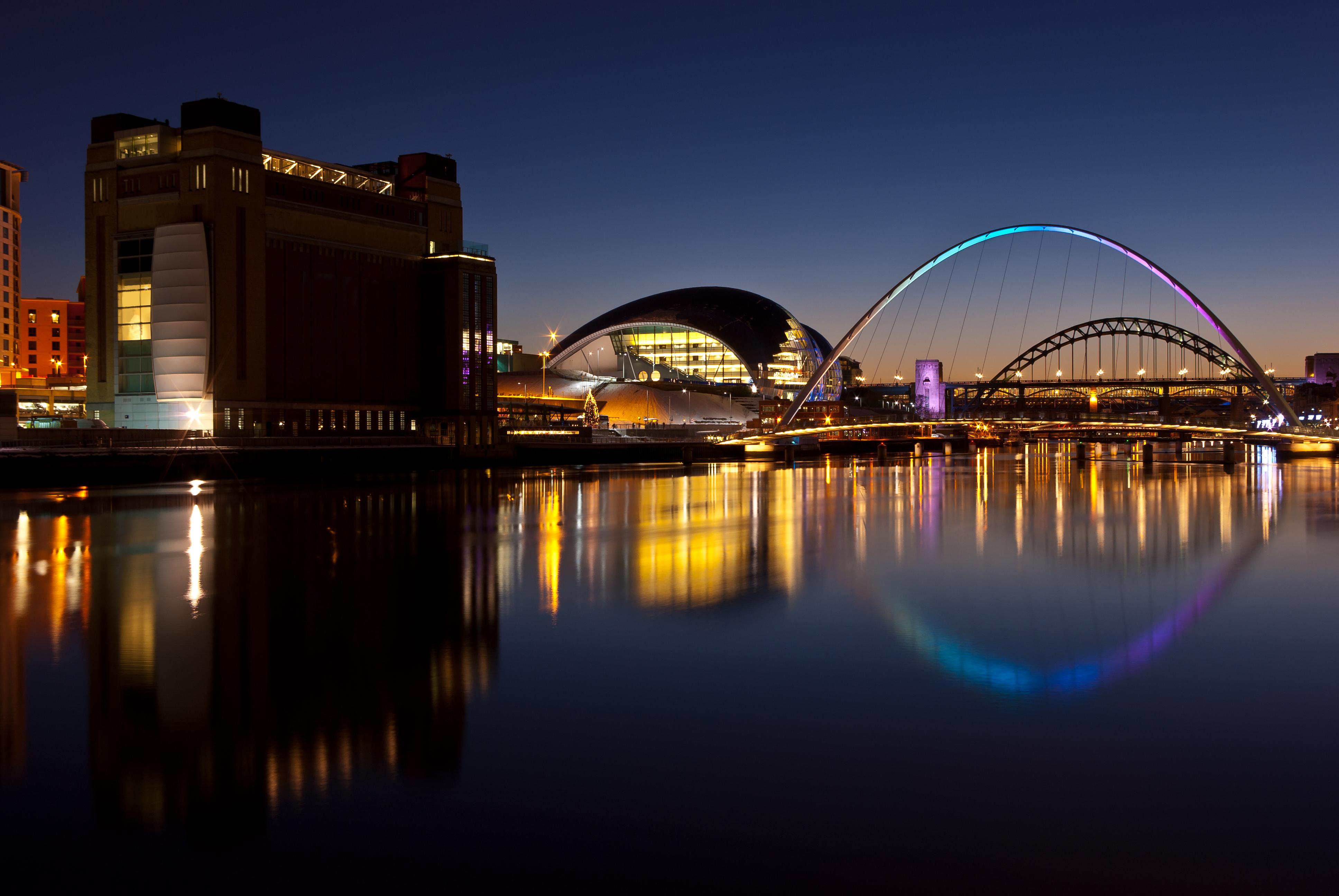 Newcastle and Gateshead at sundown showing Gateshead Millenium Bridge and Tyne Bridges