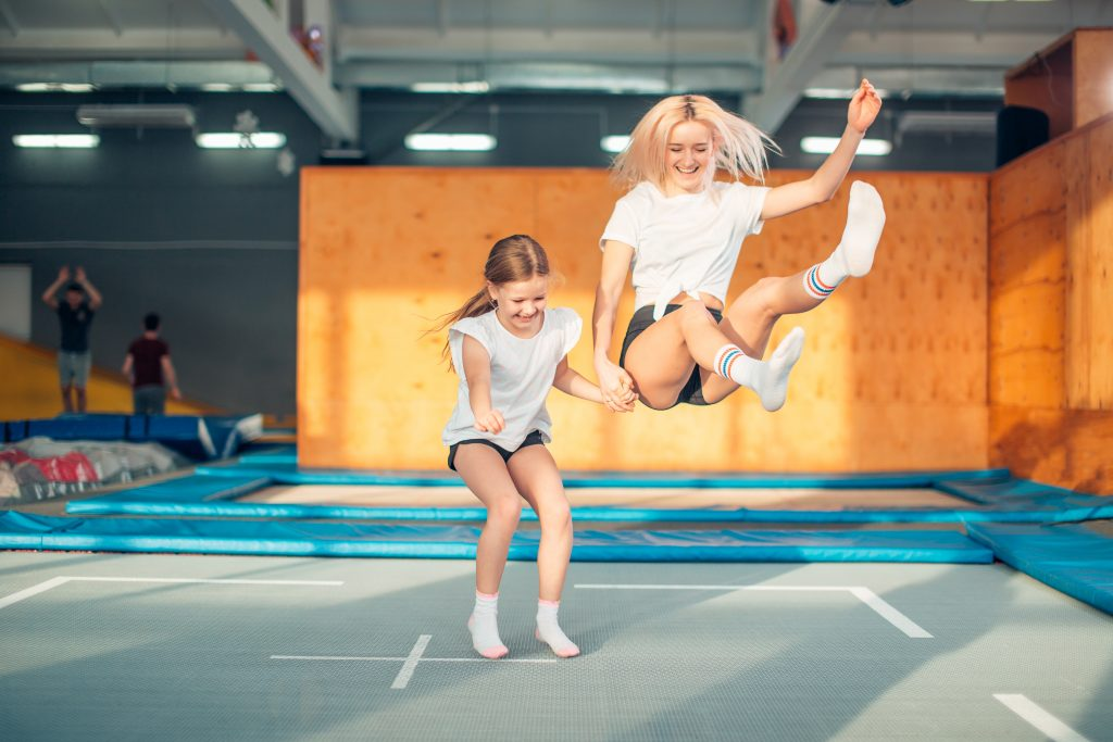 2 girls jumping on a trampoline
