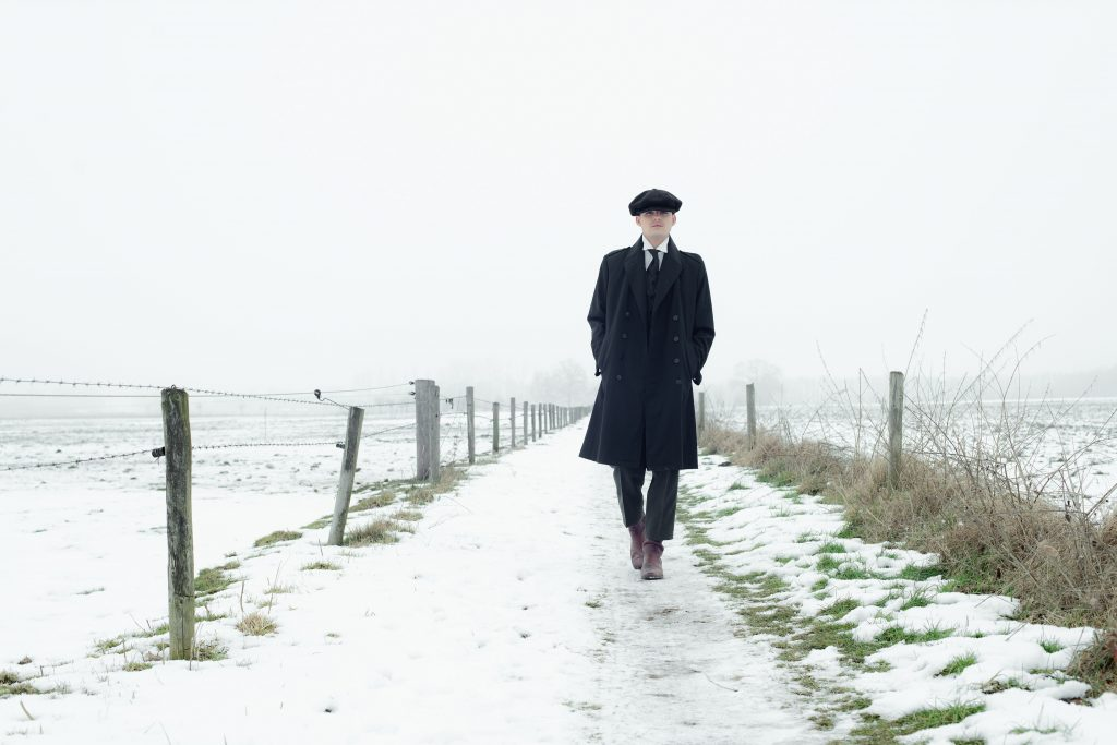 A man dressed as a peaky blinder walking through the snow