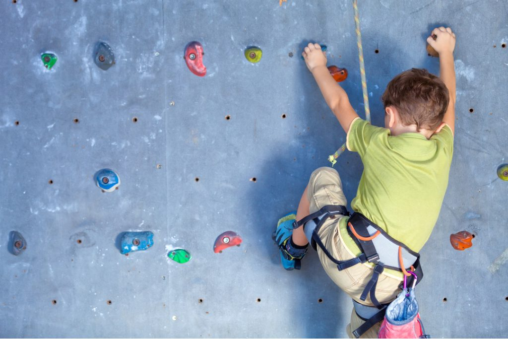 A boy with rope harness climbing an indoor climbing wall