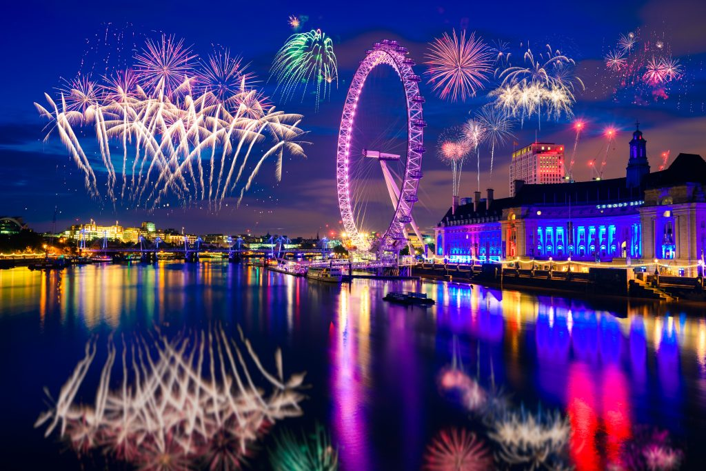 View on the London Eye on the Thames with fireworks all around