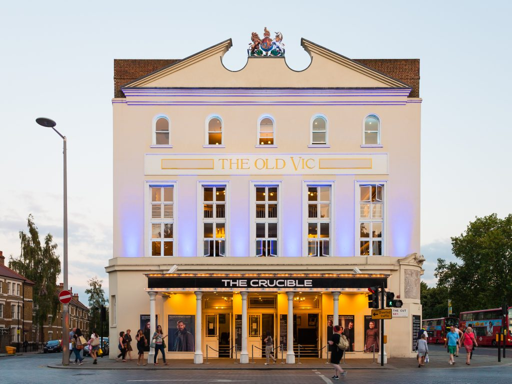A view of The Old Vic lit up at dusk