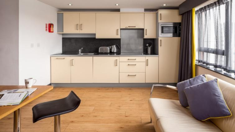 Roomzzz Leeds City West Apartments view of the fully equipped kitchen and nude coloured decor