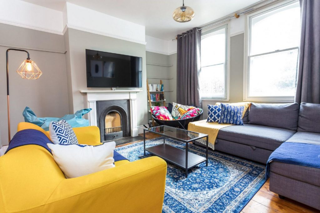 The vibrant living area of the River Cam Place with sofas and fireplace