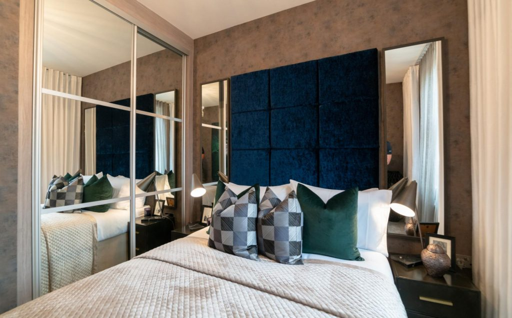 Dark blue and white bed with mirrored wardrobe