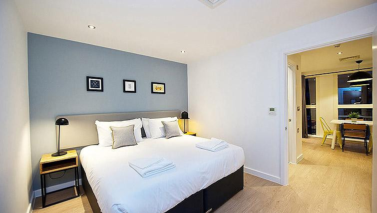 bright white bedroom with photos on a duck egg blue walll
