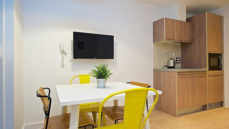White dining room table with yellow chairs and T.V. above it