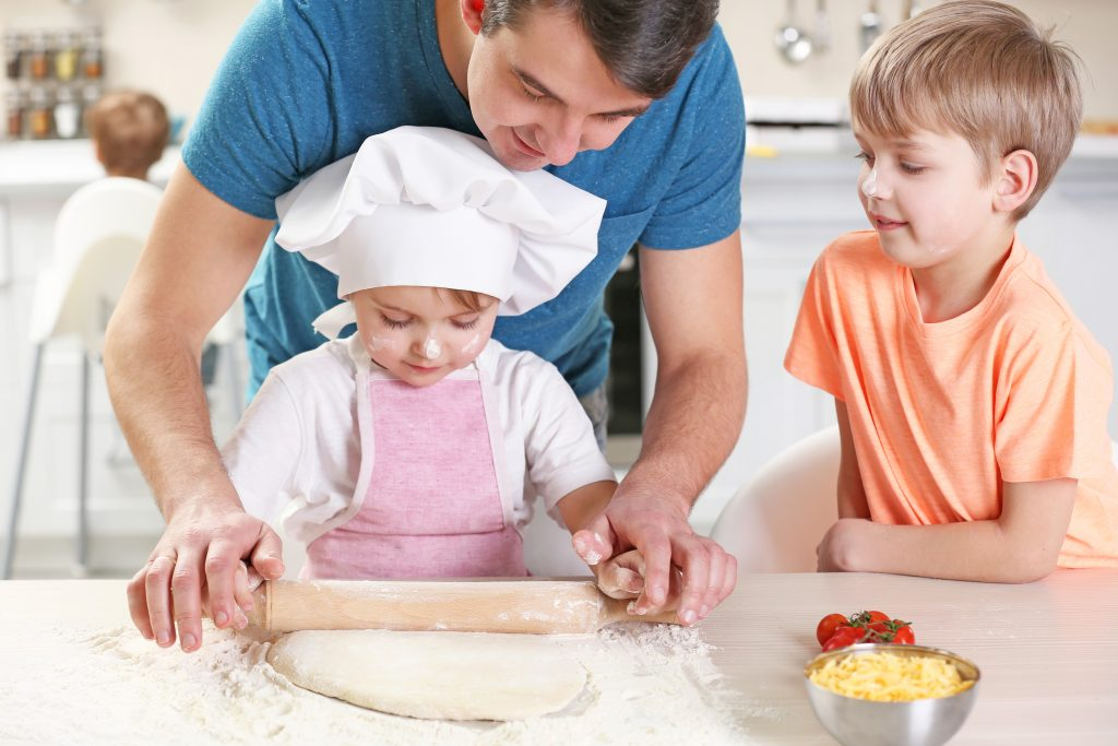 Family rolling out pizza dough together