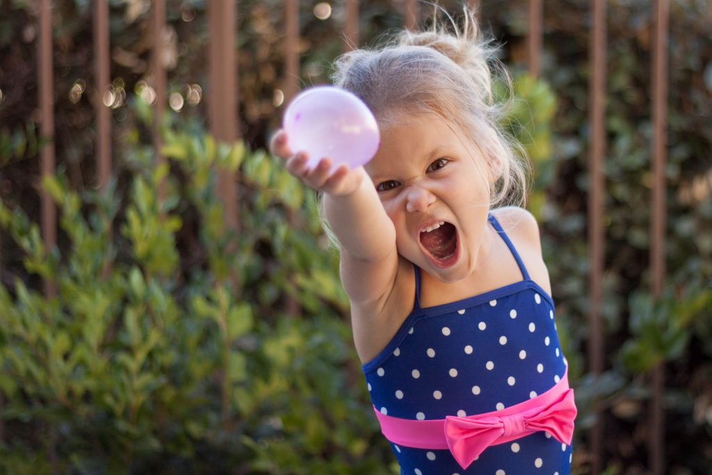 A little girl about to throw a waterbomb