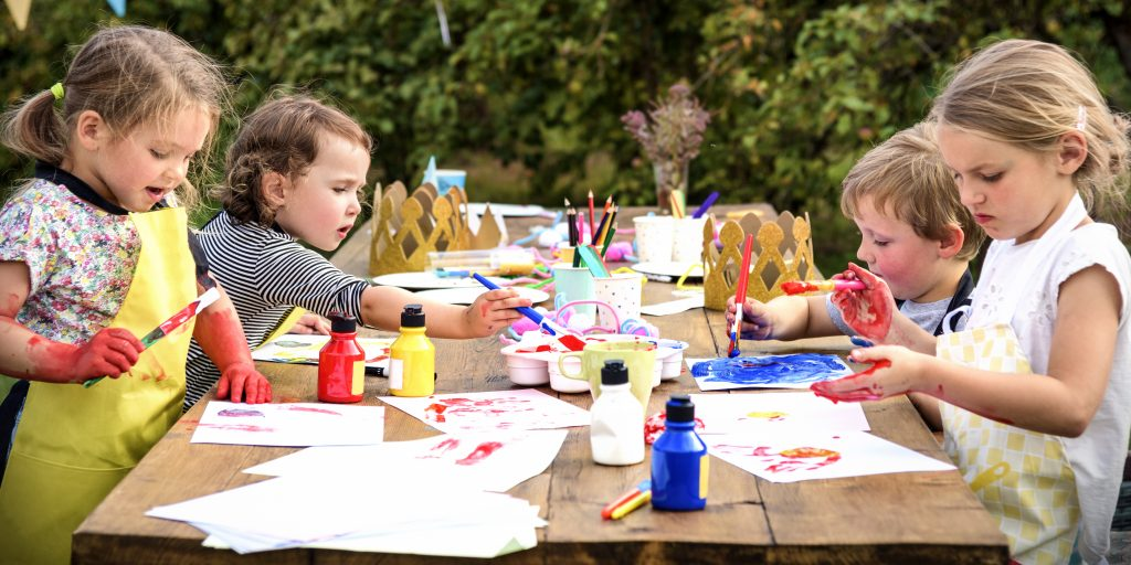 Children sat around a table creating arts and crafts