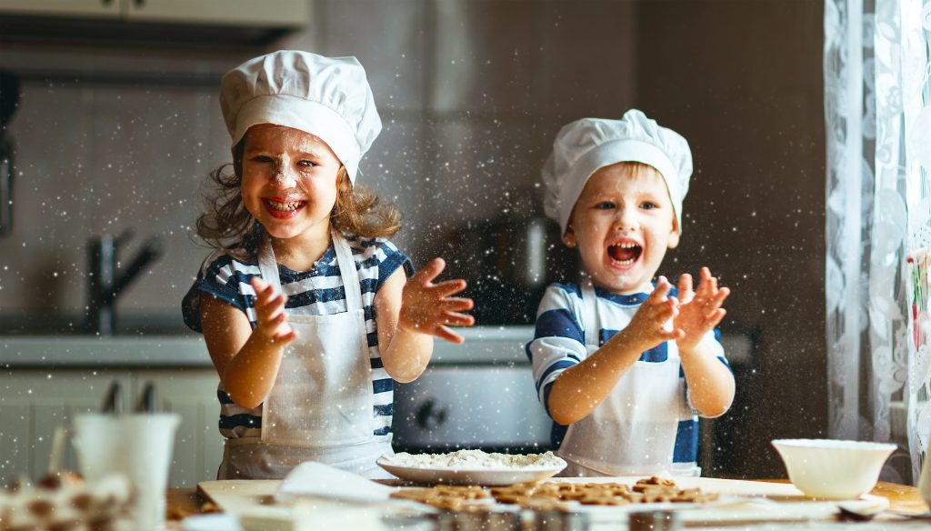Two children throwing flour around the kitchen