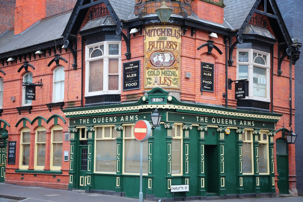 A pub front with green paint and a sign that says 'The Queen's Arms'.