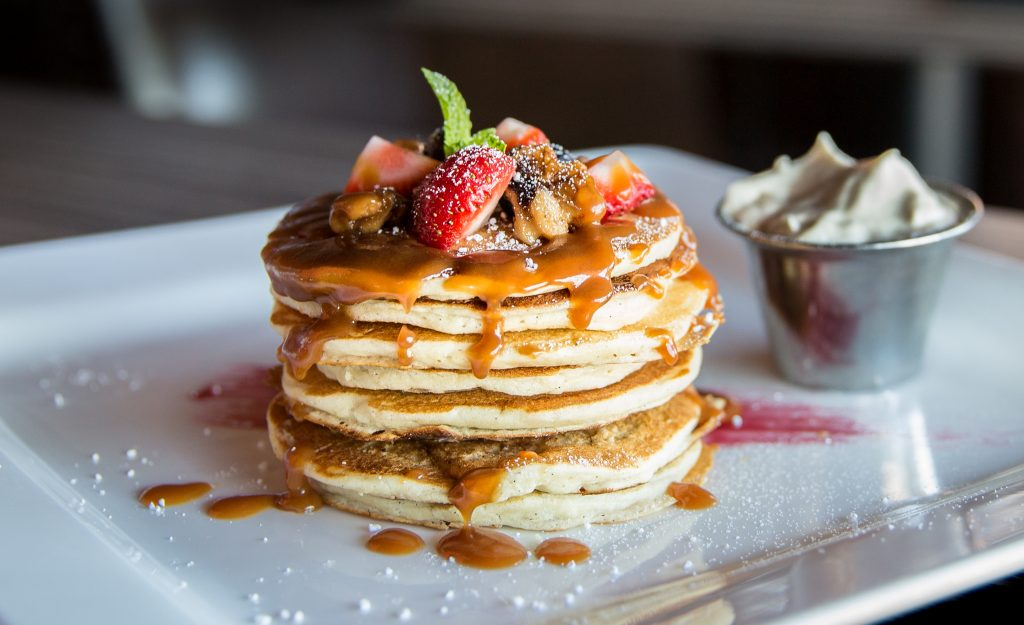 A stack of pancakes with syrup and strawberries