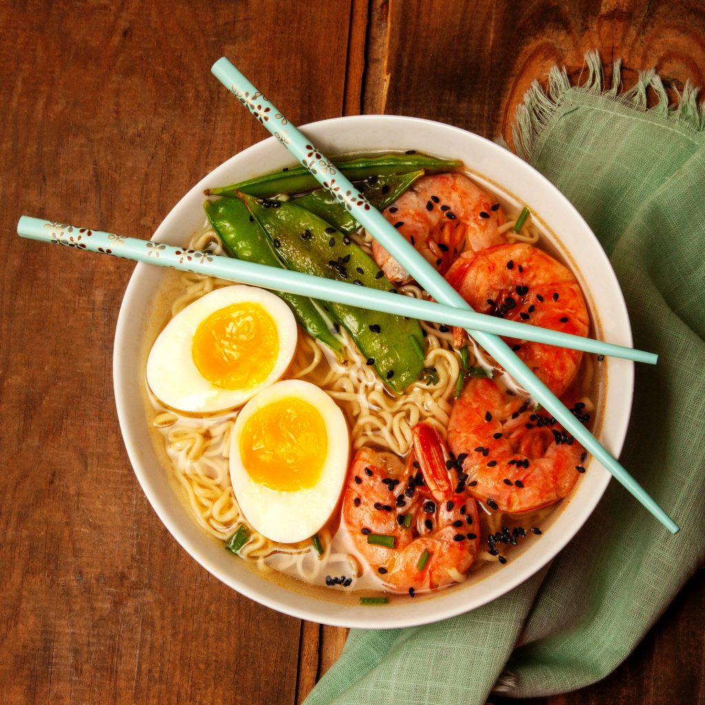 Ramen bowl filled with noodles, egg and prawns