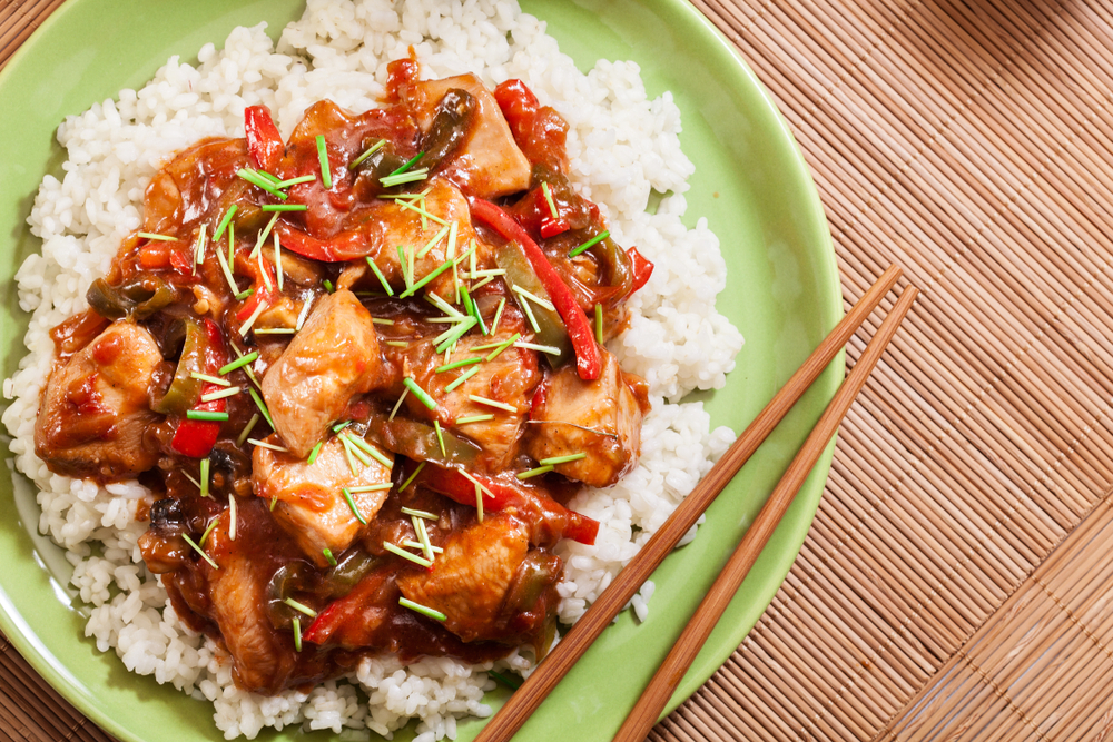 Sweet and sour chicken served on a bed of rice with chopsticks on the side.