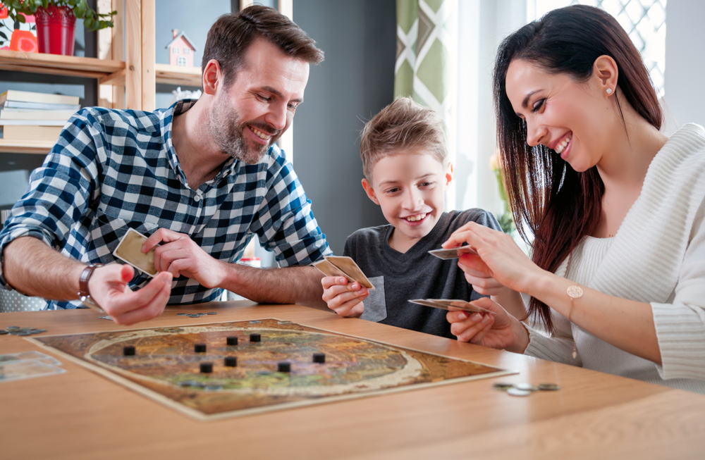 Family sat around a board game playing Codenames.