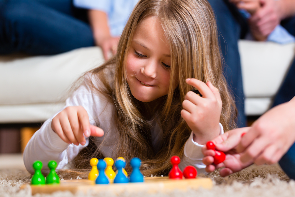 Little girl playing a board game and learning.
