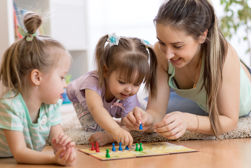 Mother helping her 2 young children to play the board game.