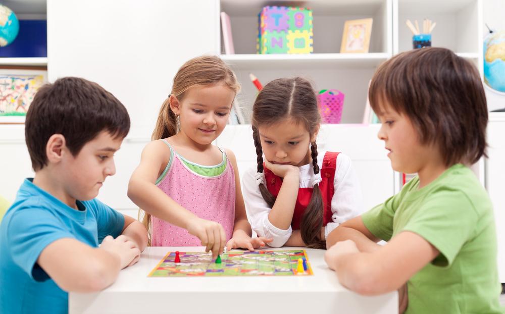 4 children gathered around a board game.