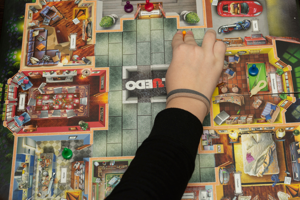 A Cluedo board with someones hand moving the pieces.