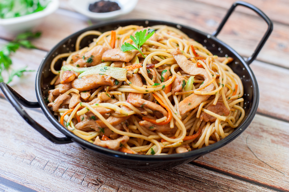 A large wok filled with noodles and spices.
