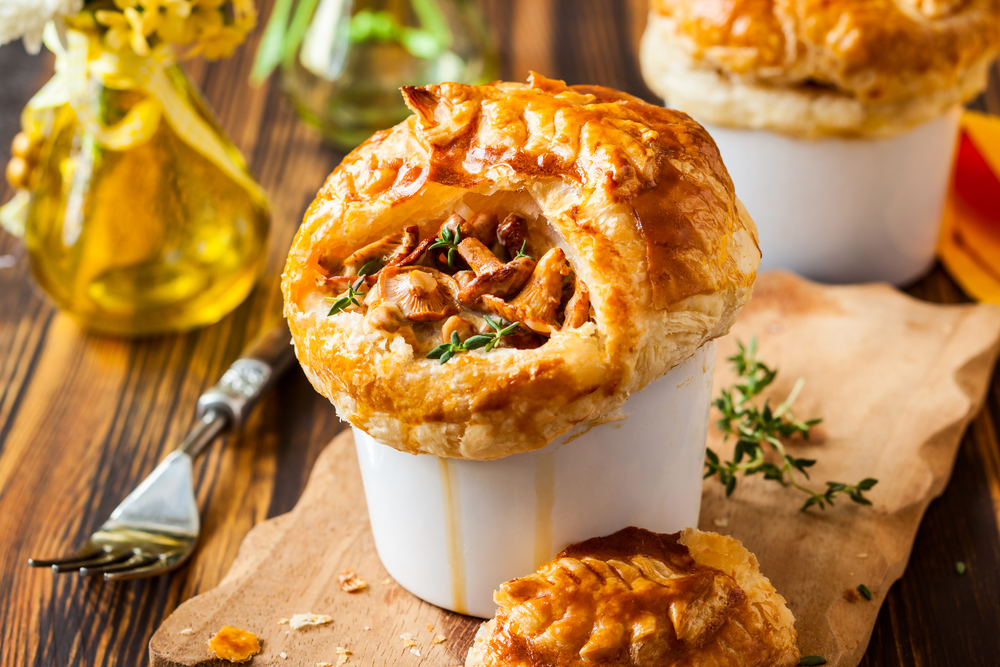 A chicken pot pie cut open to expose the chicken, mushrooms and pastry.