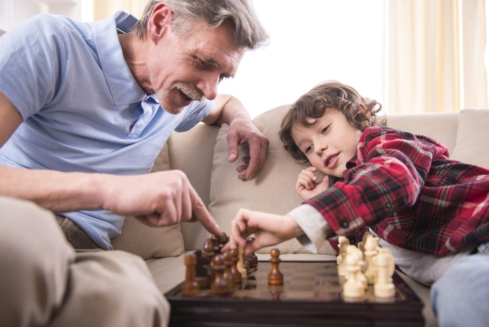 Little boy and grandpa playing chess