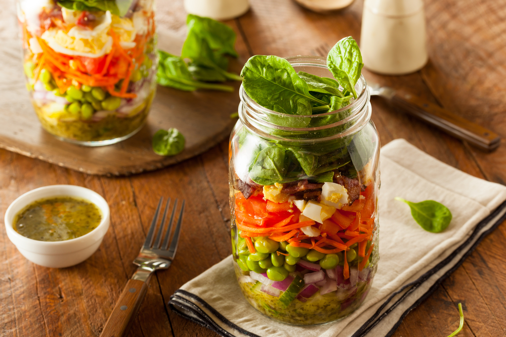 A jar filled with salad and toppings for the shrimp feta salad.