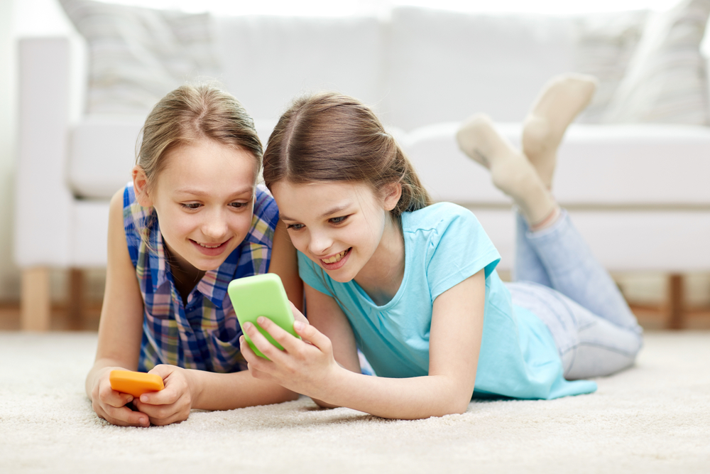 Two teen girls playing on their phones.