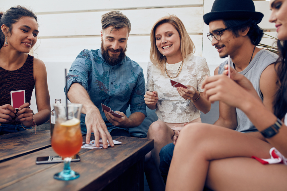 A group of friends drinking and laughing while playing the game