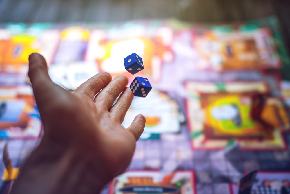A hand throwing dice across the board game