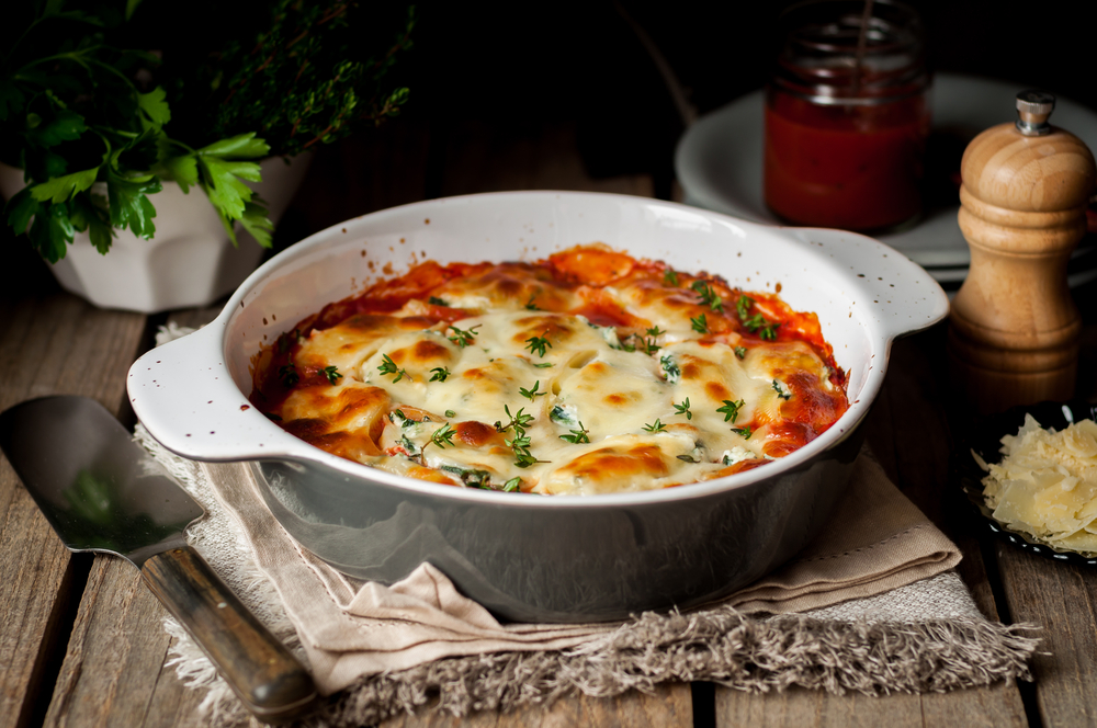 A dish filled with lasagne and topped with cheese.