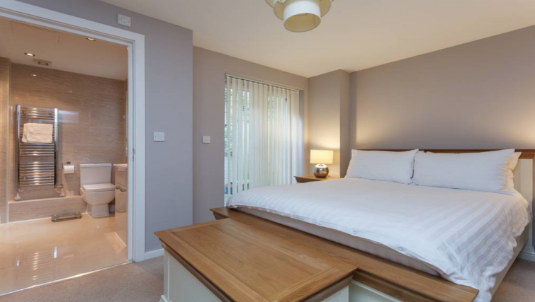 Crisp white sheets and an en-suite are the perfect combination in this Bournemouth serviced apartment