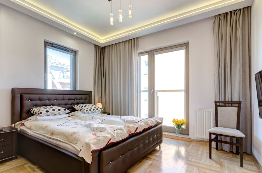 Brown bed at Waterlane Residence Apartments, Srodmiescie, Gdansk - Citybase Apartments