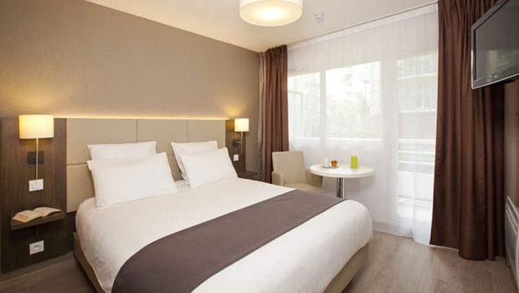 Double bed at Séjours & Affaires Grande Arche Apartments - Citybase Apartments