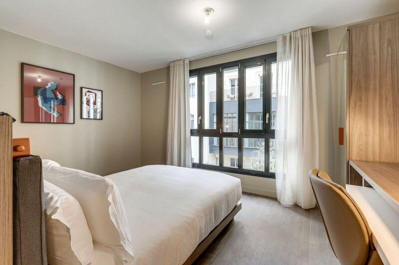 Queen size bed at Mode Arc De Triomphe Apartments - Citybase Apartments