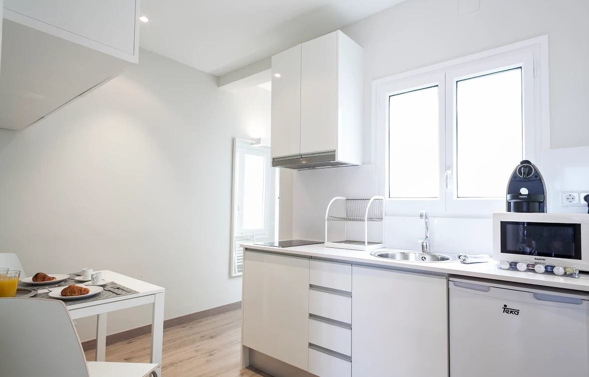 White kitchen at Sunny Serviced Apartments, Eixample, Barcelona - Citybase Apartments