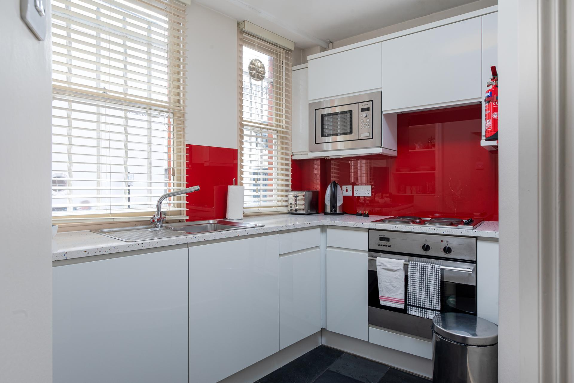 Red kitchen at Draycott Place Serviced Apartments, Chelsea, London - Citybase Apartments