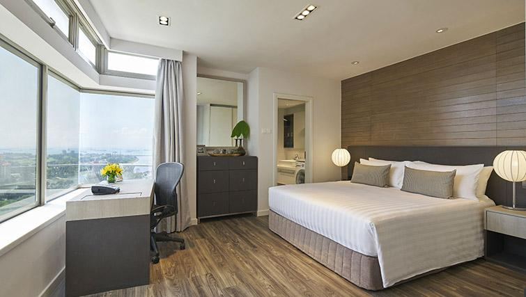 Bed and work space at PARKROYAL Serviced Suites Singapore - Citybase Apartments