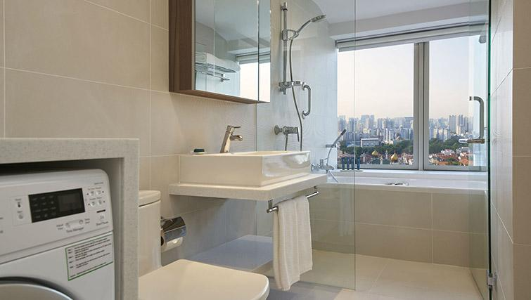 Bath and shower at PARKROYAL Serviced Suites Singapore - Citybase Apartments