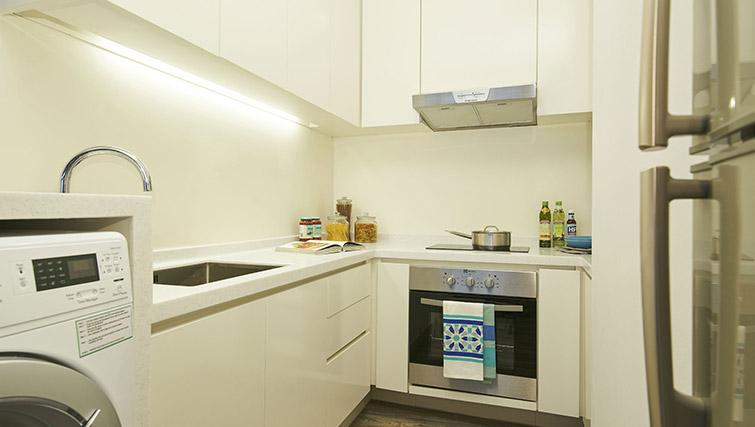 Washer dryer and kitchen at PARKROYAL Serviced Suites Singapore - Citybase Apartments