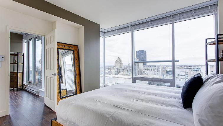 Queen size bed at Le V Apartments - Citybase Apartments