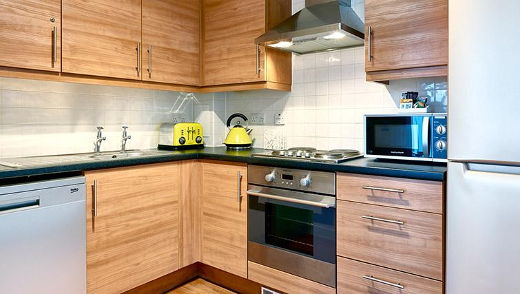 Wooden kitchen at Fully equipped kitchen at The Hub Milton Keynes Apartments - Citybase Apartments