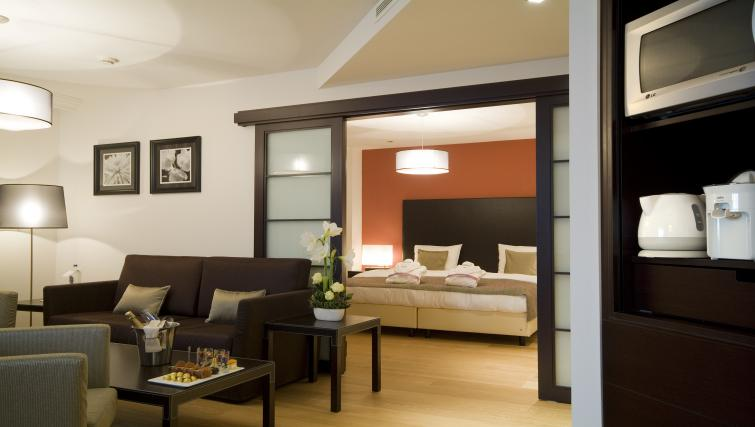 Bed and lounge area at Radisson Blu Astrid Antwerp Suites - Citybase Apartments
